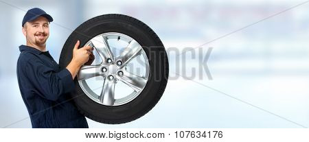 Smiling car mechanic with a tire over blue background.