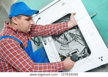 Washing machine repair. Repairer replacing electric engine motor in damaged unit