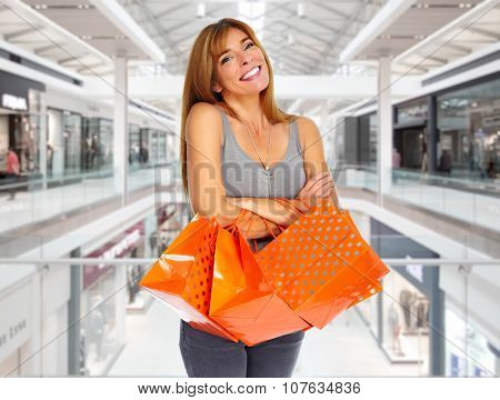 Shopping woman with paper bags in a shopping mall .