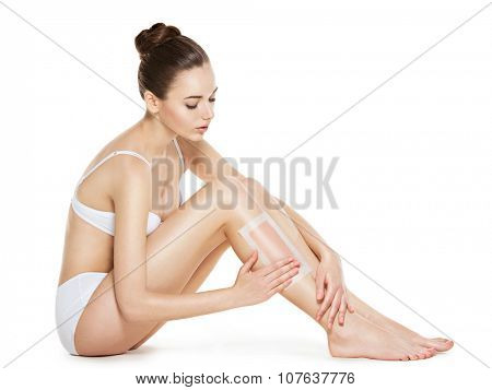 beautiful young woman depilate her legs by waxing -  studio on white background