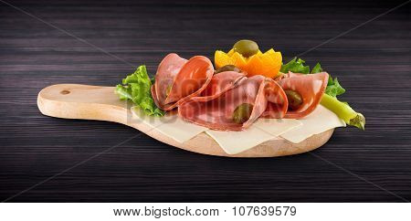 Mortadella Slice And Vegetables On Wooden Board With Clipping Path