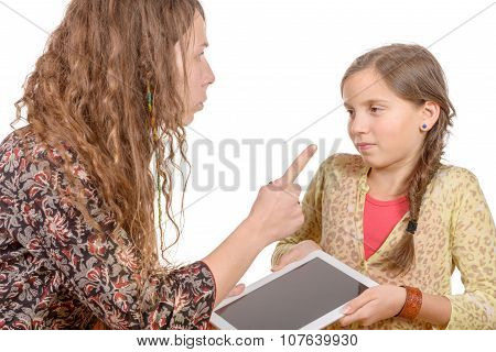 Angry mother scolding daughter because she palaying with a digital  tablet
