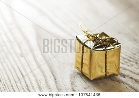 Small gift box on wooden background macro close-up