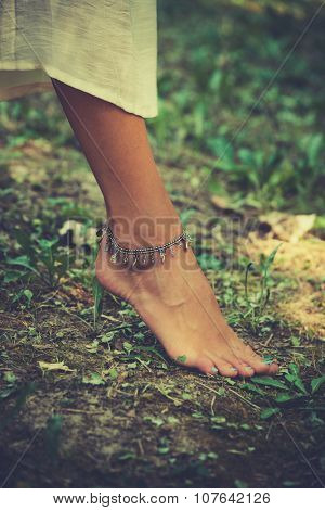 barefoot woman foot with anklet on ground, shallow depth of field