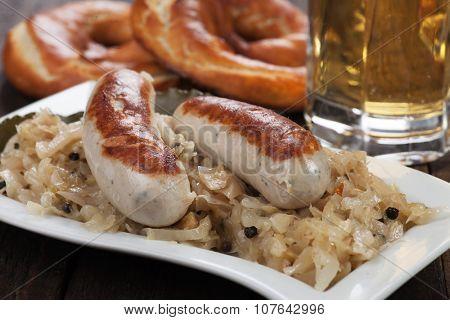 White german sausage with sauerkraut or sour cabbage and pretzel