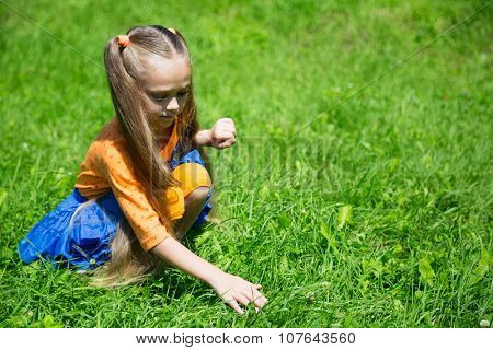 Little girl catches a grasshopper on the lawn