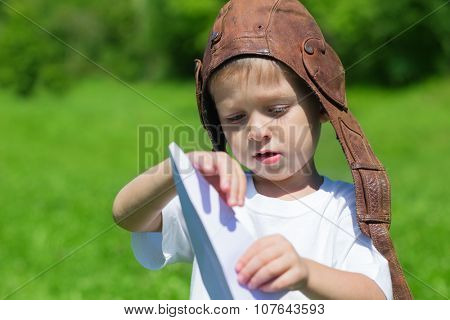 Little boy playing with a toy paper plane in park