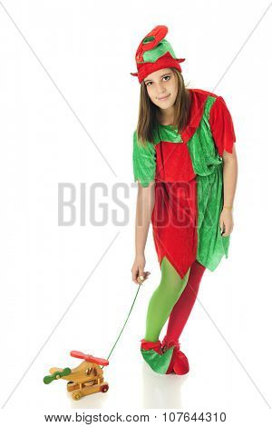 A pretty teen elf looking up at the viewer as she tests a pull-toy helicopter.  On a white background.