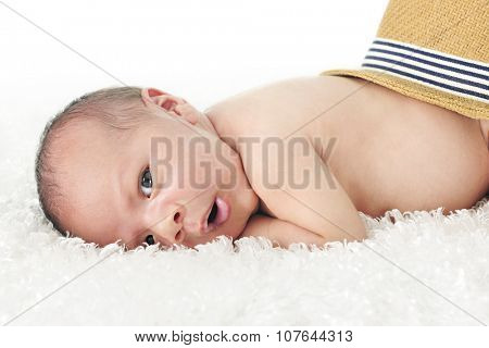Close-up image of an adorable newborn looking at the viewer as he lays on a fluffy white blanket with a straw hat on his behind.  On a white background.