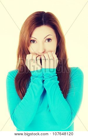Stressed young woman eating her nails.