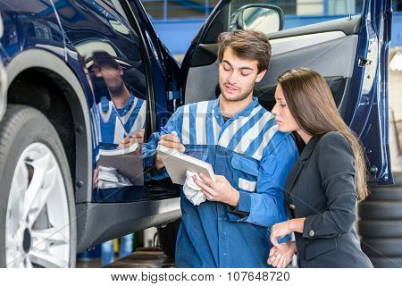 Car mechanic with female customer going through maintenance checklist in garage