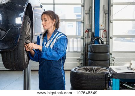 Female mechanic changing tire from suspended car at auto shop