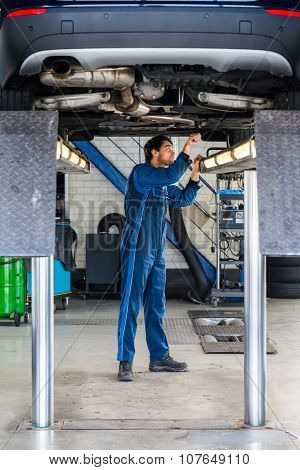 Full length of male mechanic examining under the car at garage