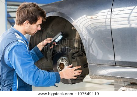 Male mechanic holding flashlight while examining brake disc of car in garage