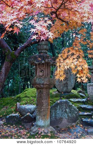 Stone Lantern And Colorful Fall Foliage At A Japanese Temple