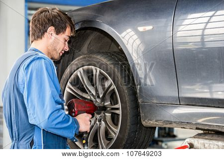 Male mechanic changing wheel on car with pneumatic wrench in garage