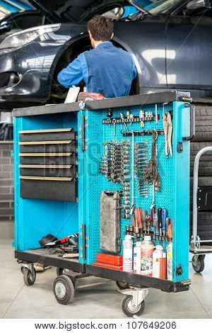 Tool cart with male mechanic repairing car in background at garage