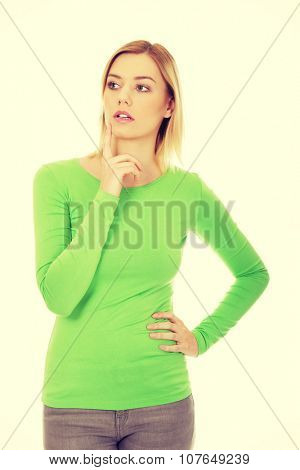 Young thoughtful woman touching chin.