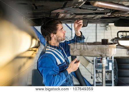 Side view of male mechanic examining car at garage