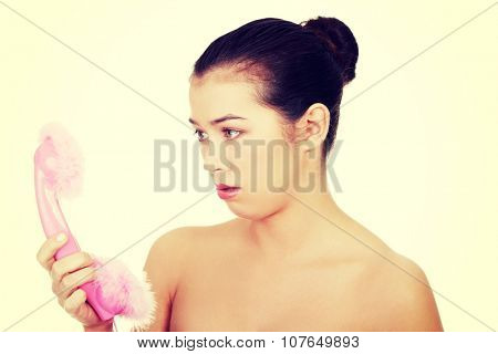 Disappointed woman looking on pink handset.