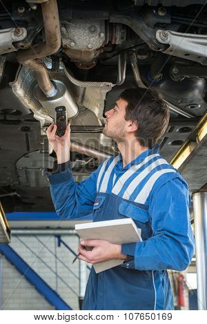 A mechanic, checing a muffler on an exhaust system of a modern car on a car lift using a LED flashlight, for gas leaks during a periodic inspection or MOT test