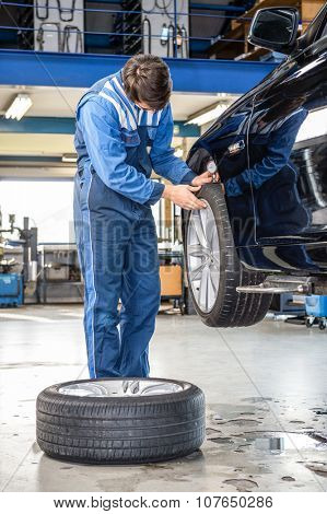 Male mechanic pressing gauge into tire tread to measure its depth at garage at garage