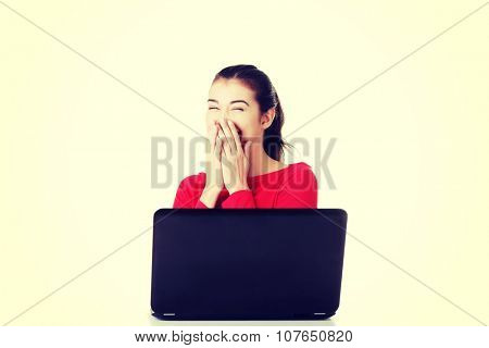Happy young woman using her laptop at the desk.
