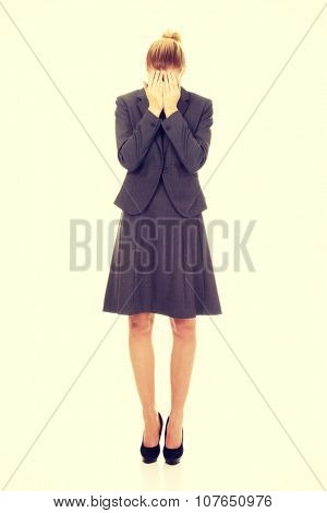 Young businesswoman covering face with hands.