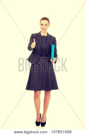 Businesswoman with thumbs up holding a binder.