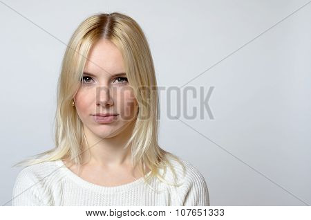 Blond Woman Staring At The Camera Against Gray
