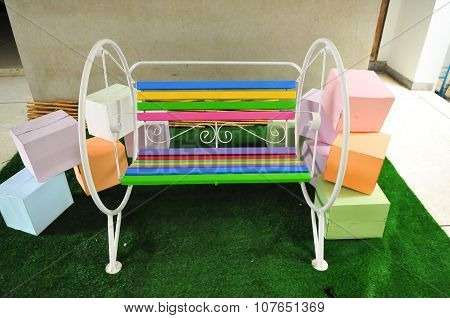 The colorful of metal chair on the green grass floor