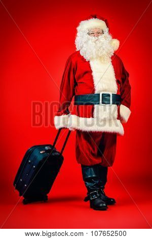 Santa Claus stands with modern suitcase over red background. Christmas time. Christmas tours.