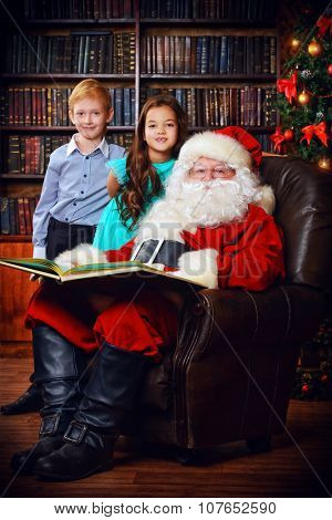 Santa Claus reading fairy tales to children. Christmas scene.