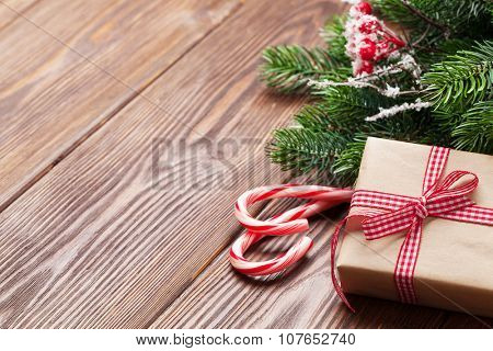 Candy cane, gift box and christmas tree on wooden table. View with copy space