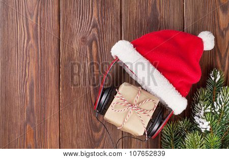 Christmas gift box with headphones and santa hat on wooden table. Top view with copy space