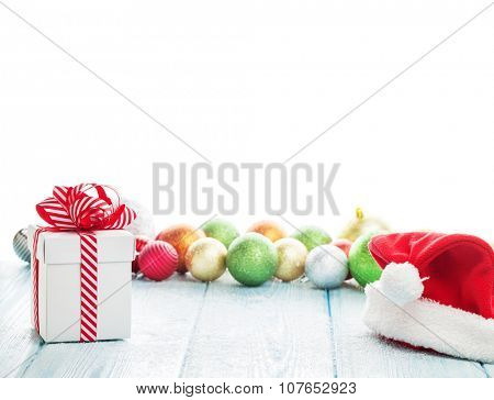Christmas gift box, santa hat and colorful baubles decor on wooden table. Isolated on white background