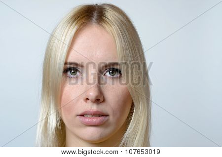 Face Of A Young Woman Against Gray Background