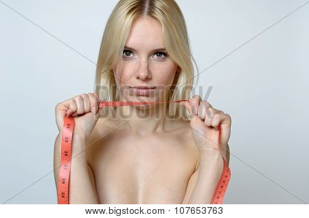 Bare Young Woman Holding A Measuring Tape