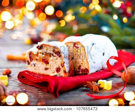 Christmas Stollen. Traditional Sweet Fruit Loaf with Icing Sugar. Xmas holiday table setting, decorated with garlands, baubles, wallnuts, hazelnuts, cinnamon sticks
