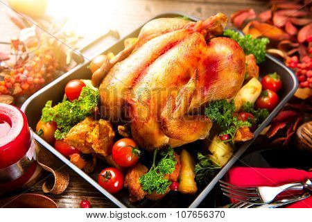 Thanksgiving Dinner. Roasted turkey garnished with Potato, Vegetables and cranberries on a rustic style table decorated with autumn leaves and candles. Christmas Dinner. Served table, table setting