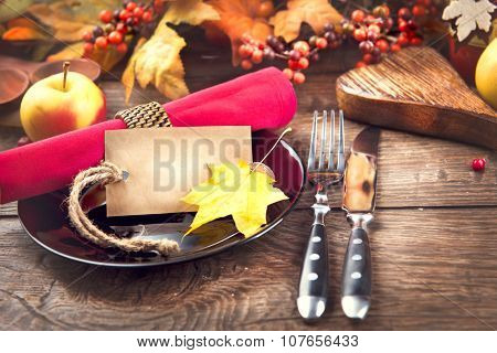 Thanksgiving Dinner. Thanksgiving wooden table served, decorated with bright autumn leaves. Holiday Table setting with invitation blank card