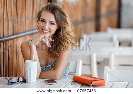 A fun and cheerful model in a summer cafe