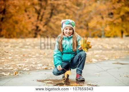 prettypretty little girl squatting with leaves in hand on autumn landscape