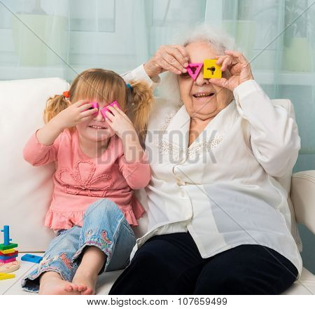 grandmother with granddaughter playing toys sitting on sofa