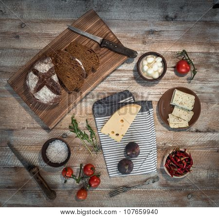 bread with cheeses and grapes and wineglass on wooden background