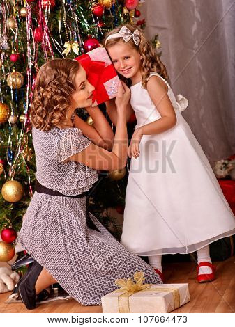 Child with mother receiving and open gifts under Christmas tree. Black and white retro.
