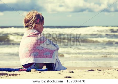Little Girl Sitting On The Beach
