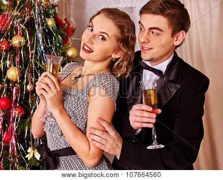 Couple on party drinking near Christmas tree. Vintage style.