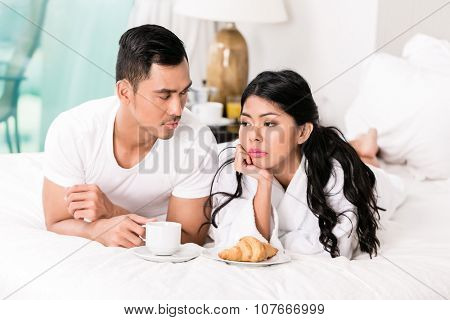 Marital issues - asian man feeling rejected by his wife, they are laying in bed