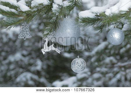 Snowy Pine Tree Branches With Sparkling Reindeer Ornament And Christmas Baubles At Wood Background